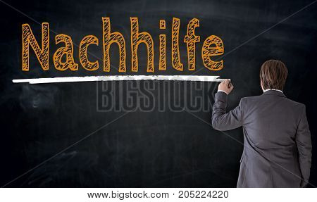Businessman Writes Nachhilfe (in German Private Turoring) On Blackboard Concept