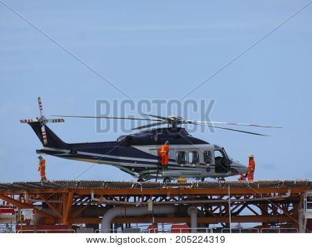 Helicopter or chopper land at oil and gas platform area for get and sent passenger from onshore hangar to offshore platform. Ground staff fill the gas tank in helicopter.