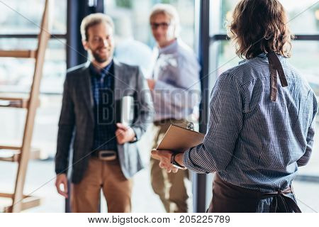 Waiter Greeting Businessmen In Cafe