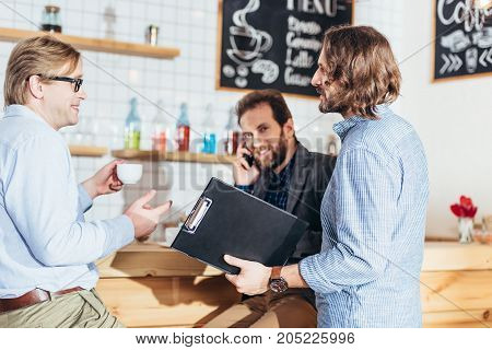 Businessmen Working And Talking In Cafe