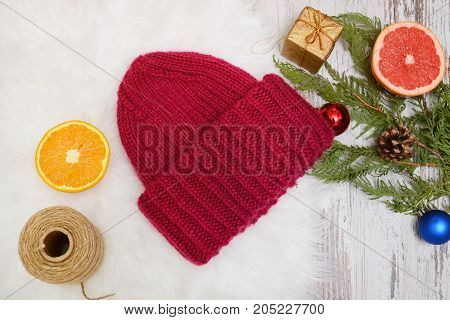New Years Concept. Burgundy Hat, Orange, Spruce Branch And Toys. White Background