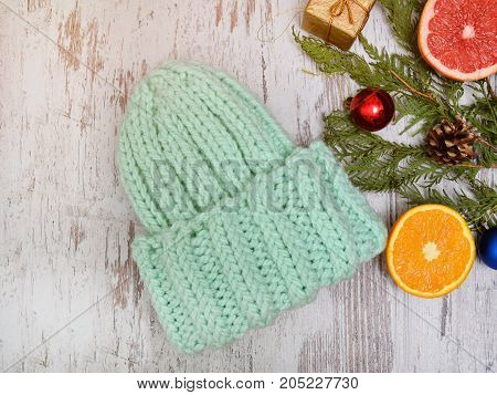 New Year's Concept. Hat Color Of Mint, Citrus And Christmas Tree Decorations. Wooden Background