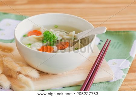 Homemade minced pork wonton soup in white bowl on wood cutting board on wood table. Delicious wonton in clear soup for breakfast or lunch or dinner.Wonton or dumpling is always popular Chinese food. Wonton soup ready to served on wood table
