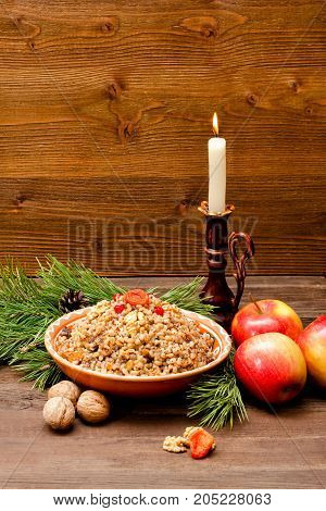 Plate with traditional Christmas treat Slavs on Christmas Eve. Spruce branch apples and candle on a wooden background
