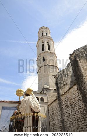 FIGUERES, SPAIN - JULY 26, 2017: Tower of church of Saint Peter and monument to the catalan philosopher Francesc Pujols in Figueres a city of Girona Catalonia Spain.