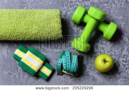 Sports And Training Idea. Dumbbells In Green Color And Apple
