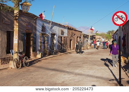 SAN PEDRO DE ATACAMA, CHILE - OCTOBER 23, 2013: Unidentified people walk by the street of the town of San Pedro de Atacama, Chile.
