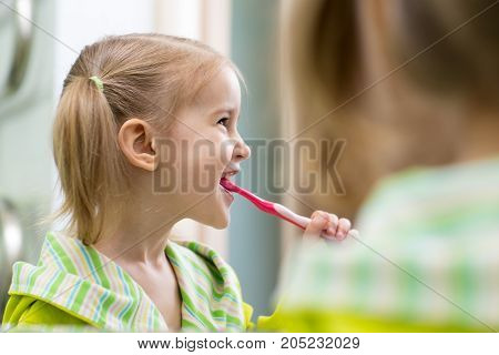 happy kid looking at mirror using toothbrush cleaning teeth in bathroom every morning and night.