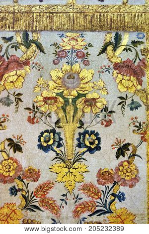 Fragment of the ancient plastered wall in Saint Francis church in Evora Portugal. Golden flowers on white field. Beautiful example of the portuguese medieval art