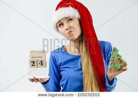 Confused young teenage woman wearing Santa Claus christmas hat holding calendar with 24 december date and christmas tree having funny grimace expression.