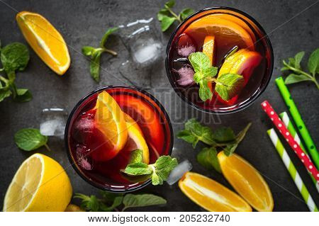Sangria with fruit mint and ice on black slate table. Top view. Traditional alcoholic cocktail. Summer drink.