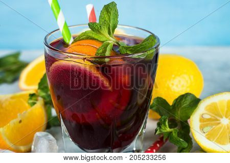 Sangria cocktail with fruit mint and ice on blue. Summer alcohol drink. Red wine.