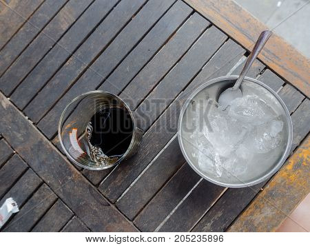 Hue, Vietnam - September 13 2017: Close up of a glass of coffee with some ice in a metallic tray, over a wooden table, view from top.
