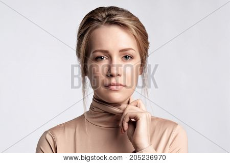 Beauty portrait of female face with professional make up. She dresses golden badloon. Looking at camera with confidence