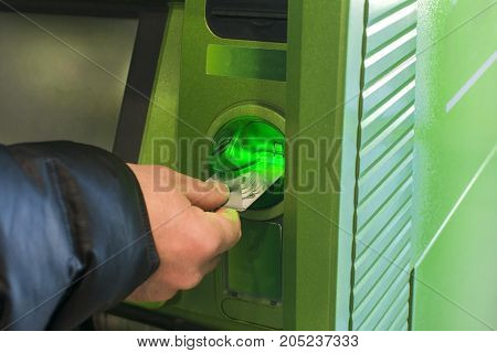 Cash withdrawal at the ATM. Credit card in hand