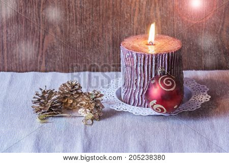 Christmas red ball candle and pine cones. Selective focus