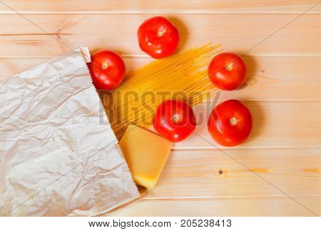 Spaghetti pasta with fresh tomatoes and parmesan cheese in paper bag