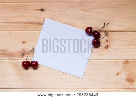 Card for notes with cherries on wooden background.