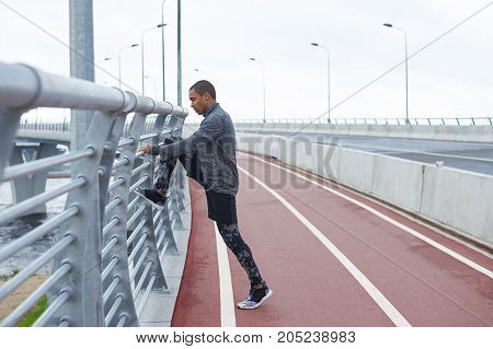Profile shot of serious young Afro American male runner in stylish sports clothes and running shoes stretching legs at stadium warming up muscles before run. Fitness sports and self-determination