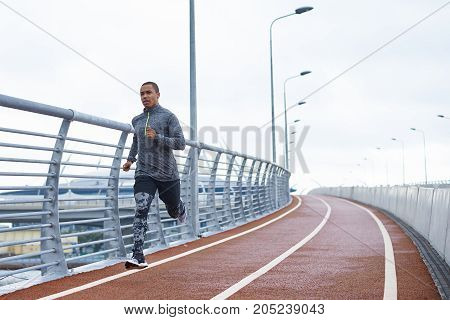 Healthy active lifestyle concept. Attractive young African male jogger exercising at stadium alone early in the morning. Muscular dark-skinned sportsman in trendy outfit getting ready for marathon