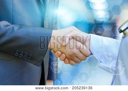 Health worker shakes hands with the patient on the blurred background.