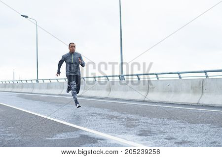 Sports people strength endurance and determination. Full length outdoor portrait of confident young African American sportsman in stylish outfit running fast along empty road training for marathon