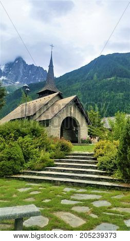 church and spire against alpine background, mossy flagstones and steps foreground