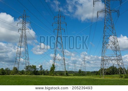 Electric pylons with electrical wires installed in a field and going to the horizon