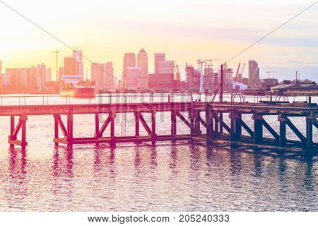 Sunset Casting A Pink Light On A Disused Jetty In London With An Approaching Ship And Canary Wharf I