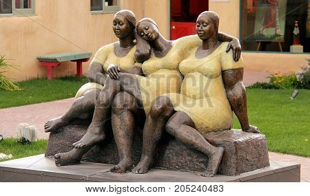 Taos, New Mexico - October 1, 2011: Street sculpture of three women in Taos, New Mexico