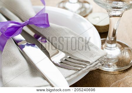 Spring Festive Table Setting With Candles. Napkin plate and cutlery on wooden table. Holidays background. Selective Focus.