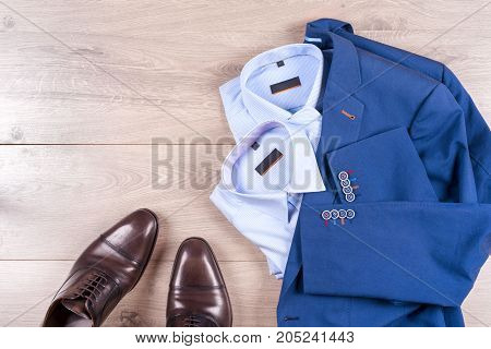 set of classic mens clothes - blue suit shirts brown shoes belt and tie on wooden background. Fashion. Men's accessories set. Top view. Copy space for text.