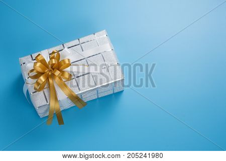 Silver white gift box with gold and white ribbon bow on blue background top view