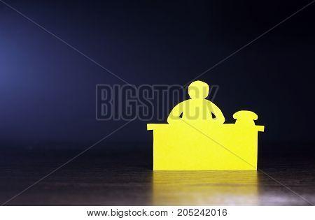 Paper man bureaucrat sitting on table against dark background