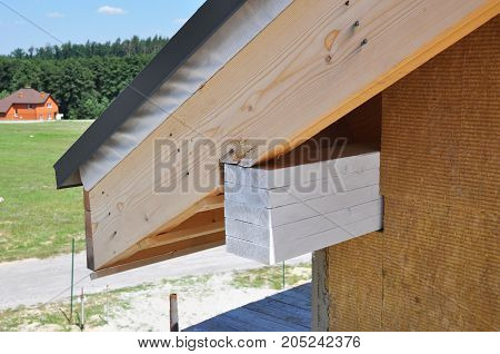 Corner of house with eaves against summer background. Install soffits, fascia, attic insulation. Roofing construction.