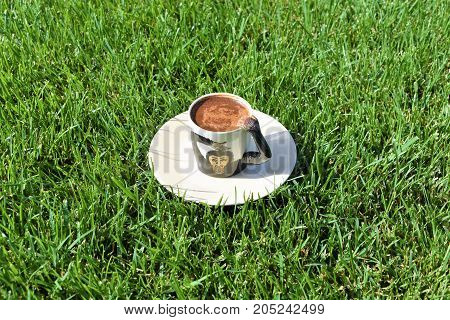 Turkish coffee background. coffee grounds on the bottom of the mug. a cup on the grass. green meadow and white tableware. fortune telling, monkey cup, monkey background, funny and cute cup, green background