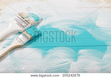 the brush with paint on wooden background