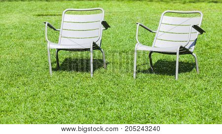Metal Chairs Stand On Fresh Grass In Summer Park