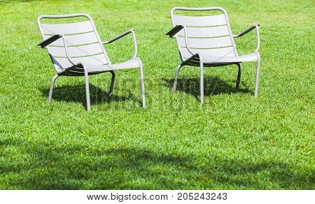 Outdoor Gray Metal Chairs Stand On Fresh Grass