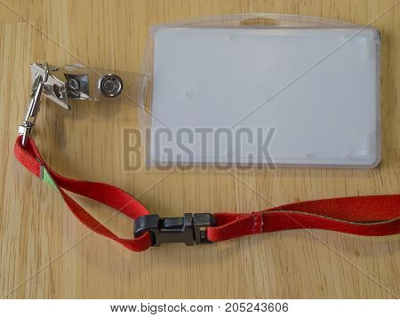 company identification card empty white name tag in plastic with red cord on wooden background