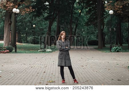 Teenage girl in grey knitted coat and black denim trousers standing in empty park. Autumn mood