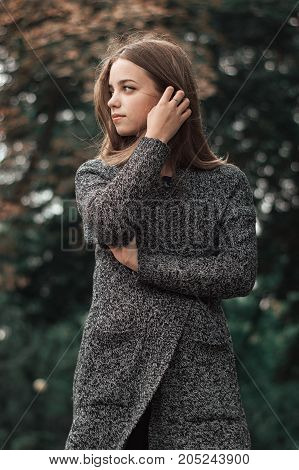 Portrait of beautiful female teenager standing in the park in warm knitted coat. Autumn season