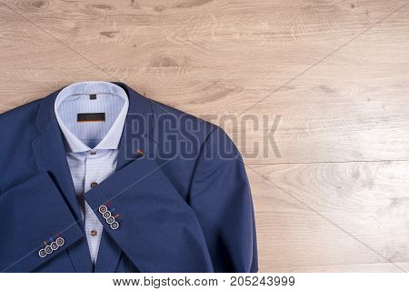 Set Of Classic Mens Clothes - Blue Suit, Shirts, Brown Shoes, Belt And Tie On Wooden Background.