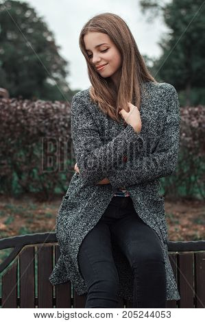 Vertical portrait of teenage girl in grey knitted coat and black denim trousers sitting in the park
