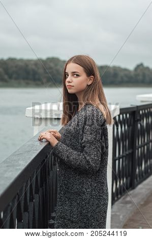 Vertical portrait of female teenager with blond hair and blue eyes standing at the bridge near river