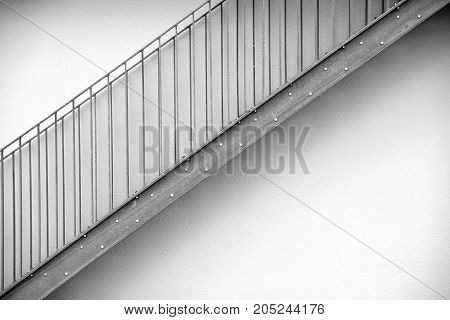 Detail of a modern exterior staircase in front of symmetrically arranged fences.
