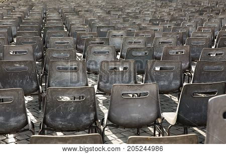 Rows of empty gray plastic chairs in an open sunny place.