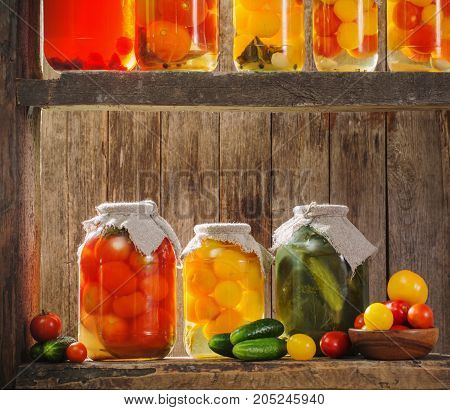 the canned vegetables in jars on wooden background