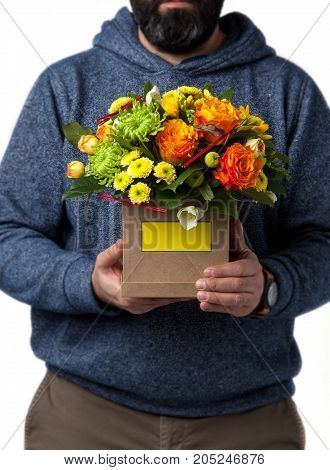 man holds assortment flowers in cardboard box. Valentine's Day