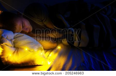 handsome guy hipster sleeping in her white bed in the night dream about happy life
